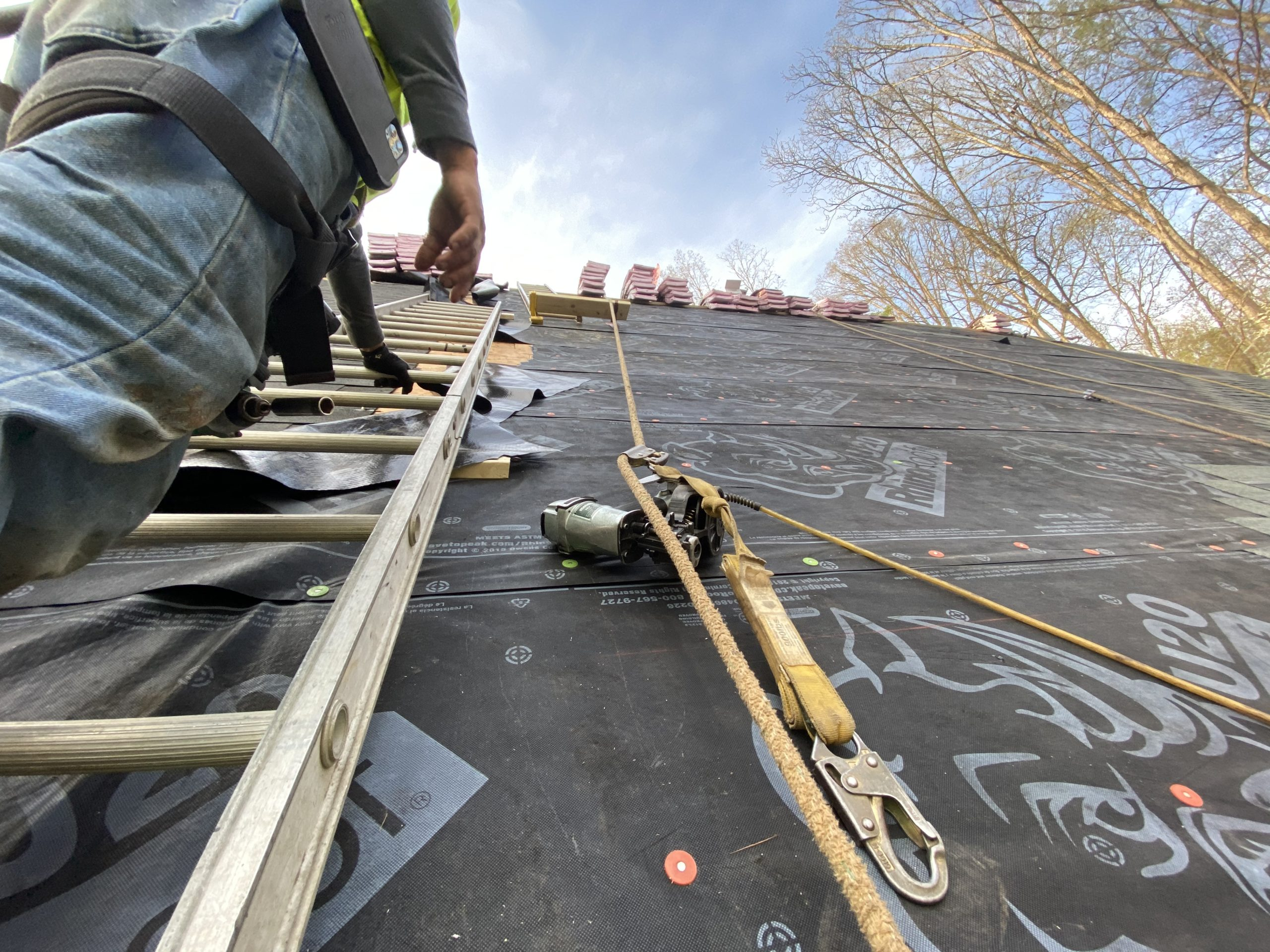 The man installing the shingles in the roof.