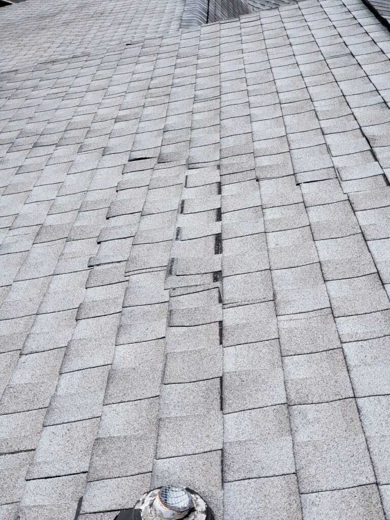 This is a picture of Gray shingles on a roof. They are now beginning to slide out from underneath other shingles.