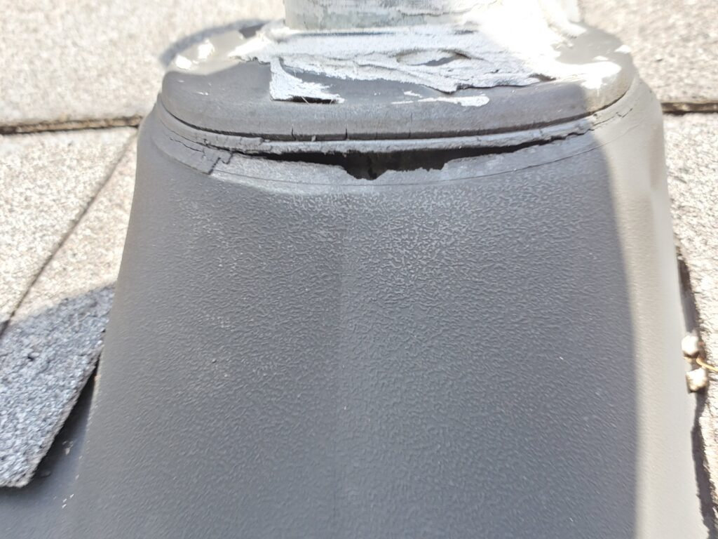 This is a picture of a pipe boot on a roof it is made of plastic the top part is made of rubber and it is dry rotting and cracking