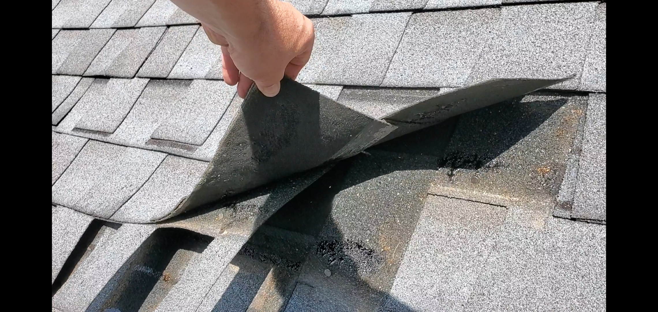 This is a picture of Gray colored shingles that are becoming separated from one another through a process called DE lamination