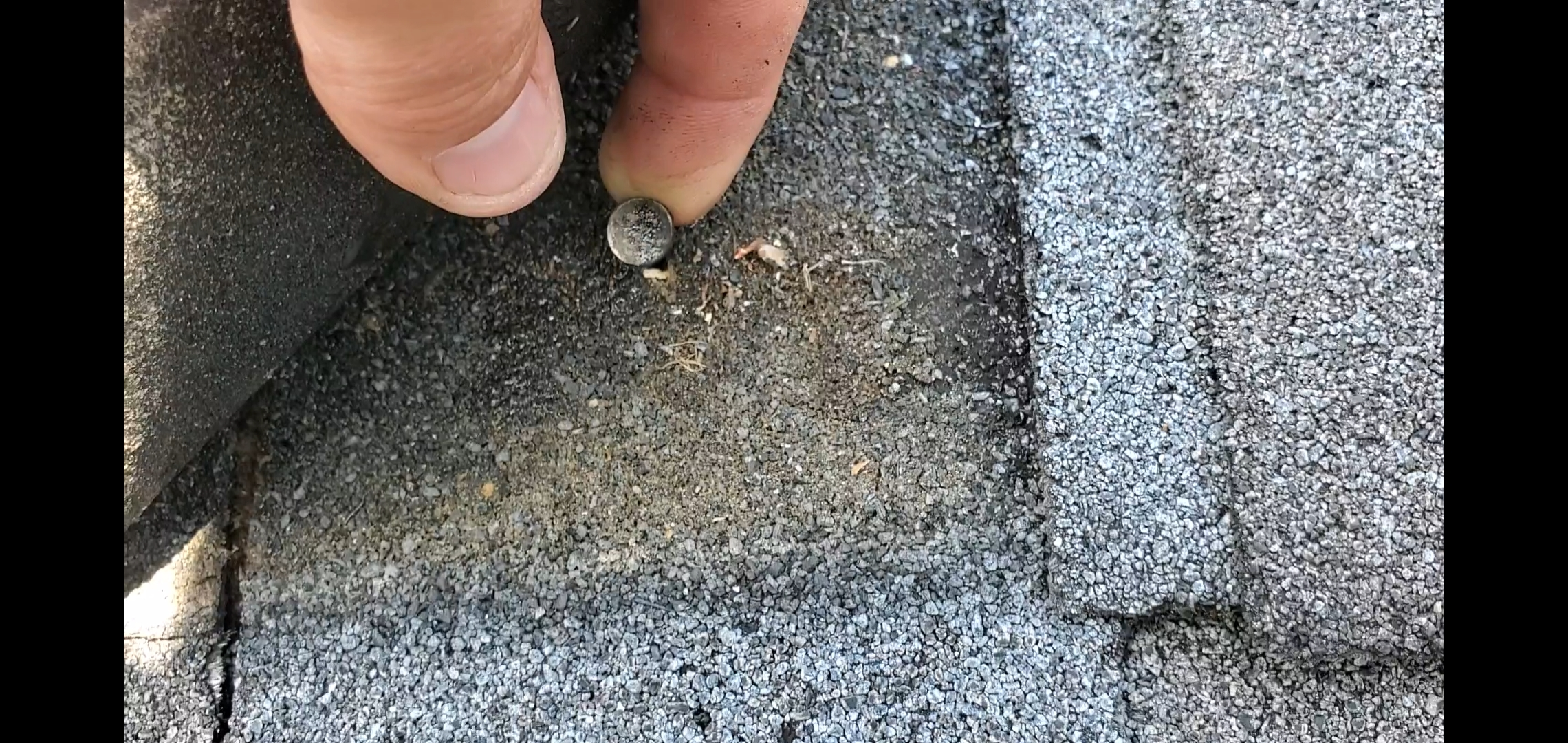 This is a picture of a nail in a single. The Nail should be much lower on the shingle in the nail strip. This nail is considered to be high nailed.