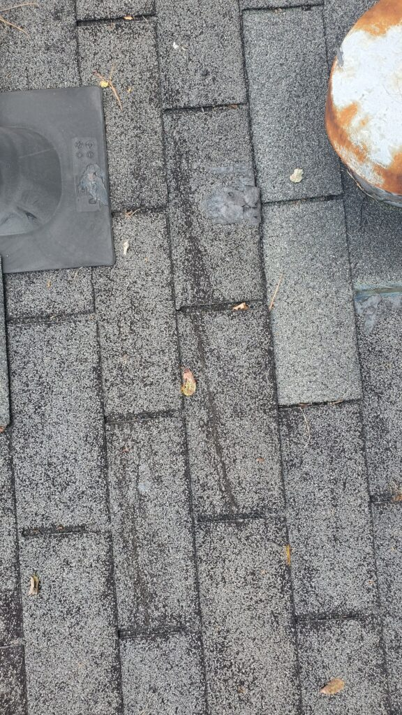 This is a close up picture of some grey shingles that are Cracked down the middle due to high winds