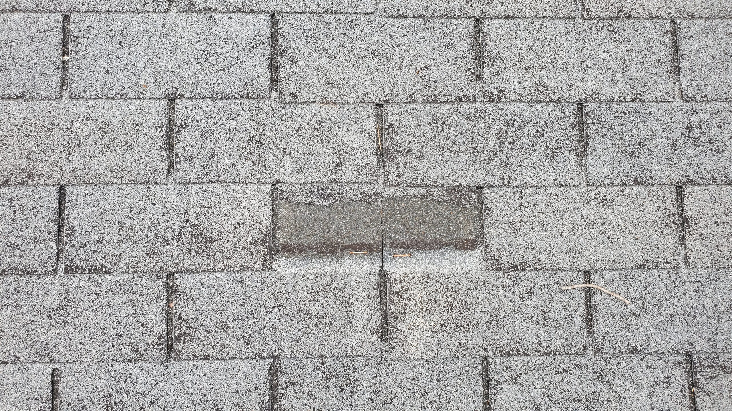 This is a close up picture of a small section of grey shingles And one of the shingles is missing