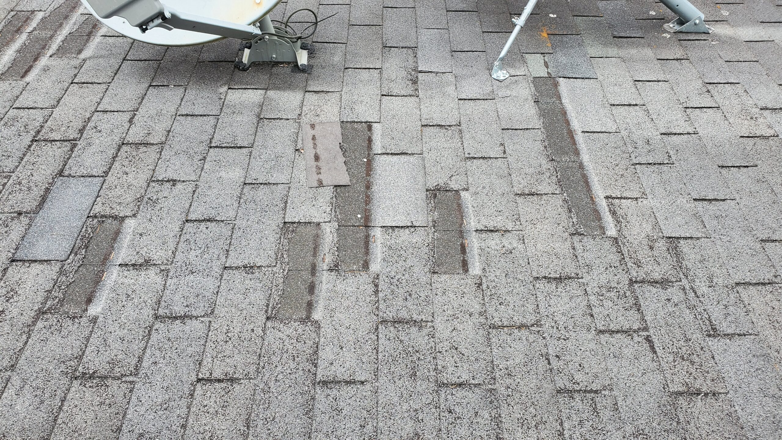This is a picture of grey shingles on a roof and many of the shingles are missing and cracked or broken.