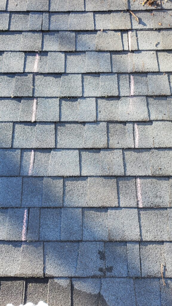 This is a picture of grey shingles with Pink lines on the representing where the edge of each shingle comes to