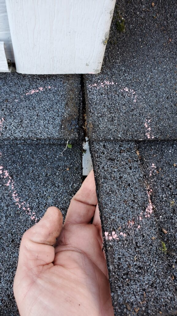 This is a picture of my hand under a shingle holding it up