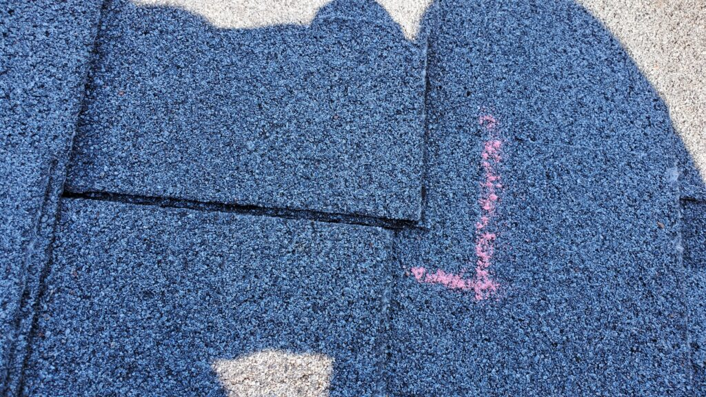 This is a up close picture of a grey shingle roof that has a area outlined in pink that shows a shingle out of place