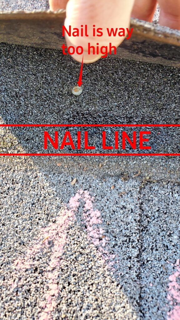 This is a picture of a shingle that has been lifted up to expose the nails under it. There is a red line that says nail line