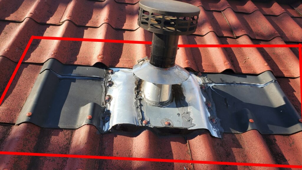 This is a picture of a red terracotta roof that has a small chimney stack Coming through it. There are red lines bordering around the chimney stack