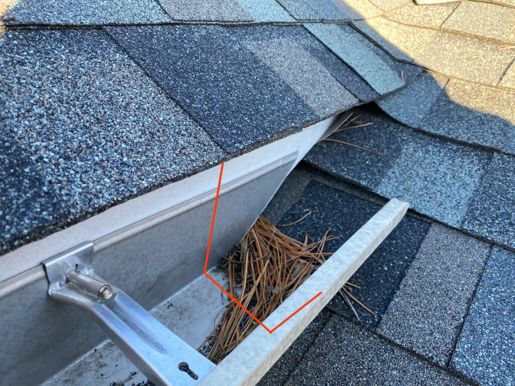 This is a picture of a downspout with no end cap and is wide open allowing water to empty out onto the roof. This allows water go go under the shingles causing a leak.