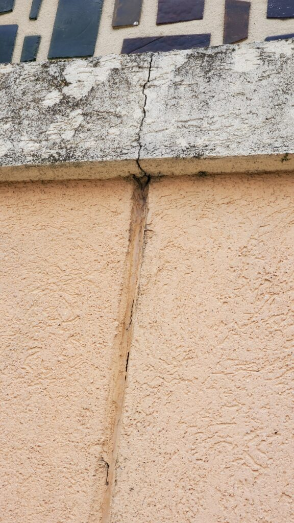 This is a crack in a concrete wall running up the front wall of a church.