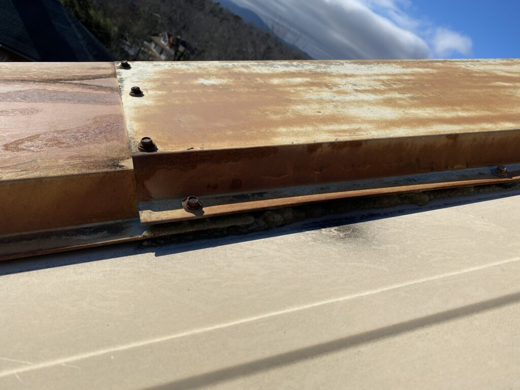 This is a view of metal roof panel that has a gap and pulling from the other panels.