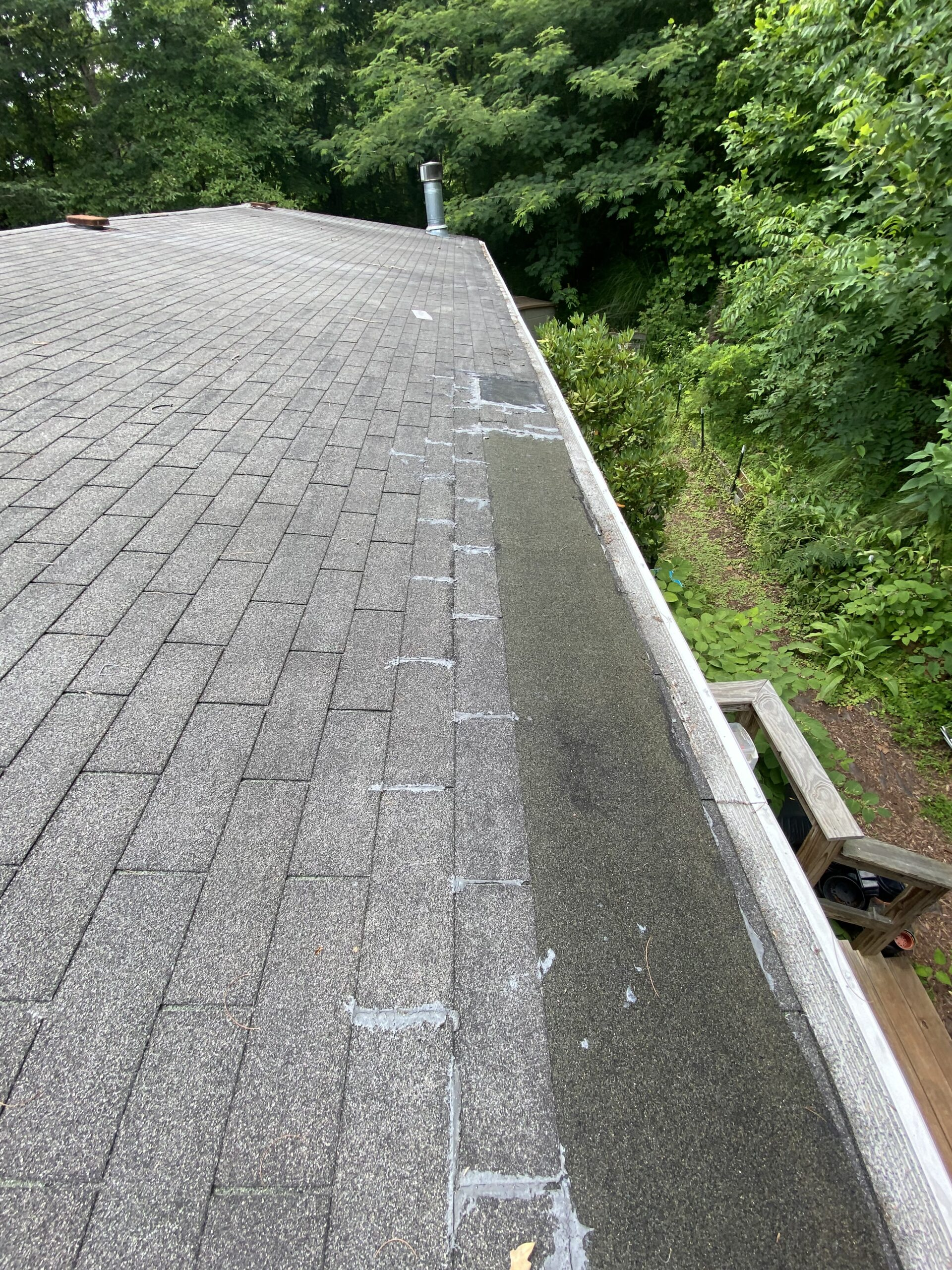 this is a picture of the edge of a roof with a sheet of ice and water shield over the shingles